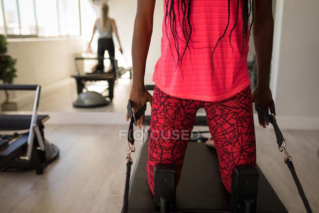 Средняя секция женских упражнений на тренажере в фитнес-студии — стоковое фото
