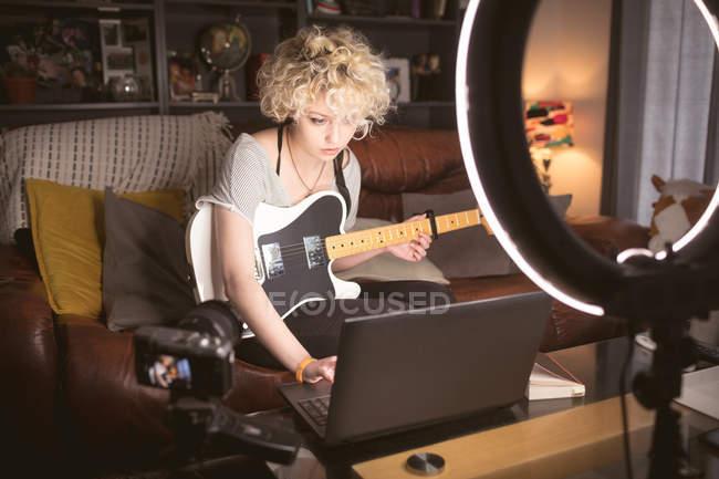 Blogueuse avec guitare utilisant un ordinateur portable dans le salon à la maison — Photo de stock