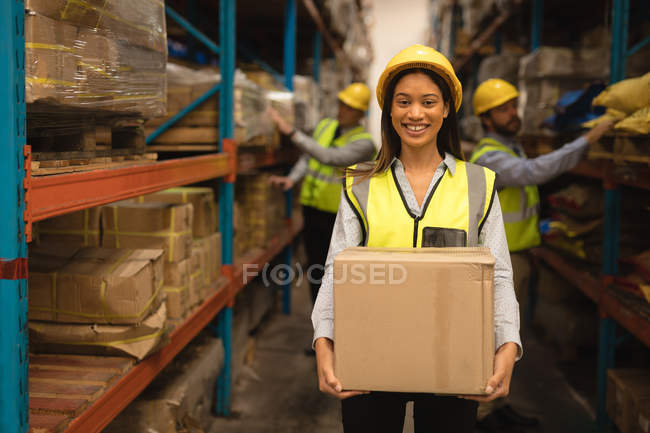 Portrait of female Staff holding cardboard box in warehouse — Stock Photo