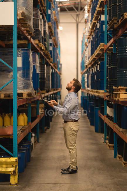 Мужчина-менеджер с помощью ноутбука при проверке запасов на складе — стоковое фото