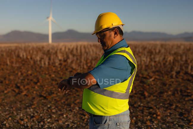 Engenheiro usando um relógio inteligente em um parque eólico — Fotografia de Stock