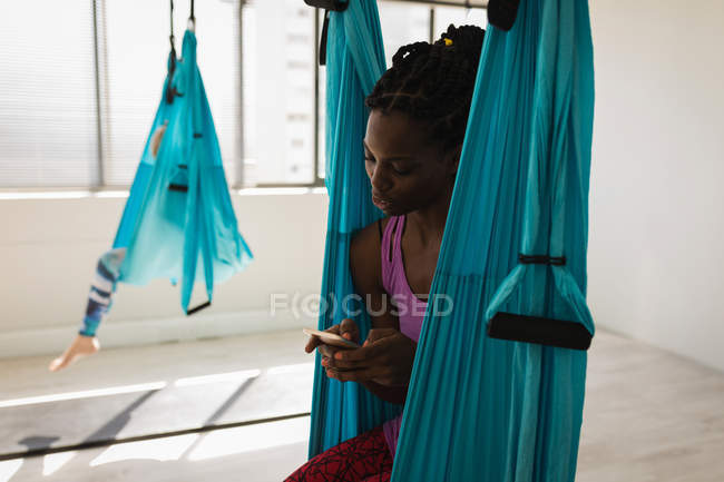 Woman using mobile phone while sitting on swing sling hammock in fitness studio — Stock Photo
