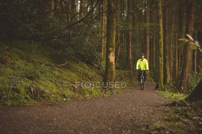 Молодой человек катается на велосипеде в лесу — стоковое фото