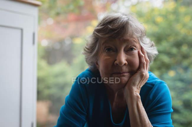 Close-up of happy senior woman looking at camera at home — Stock Photo