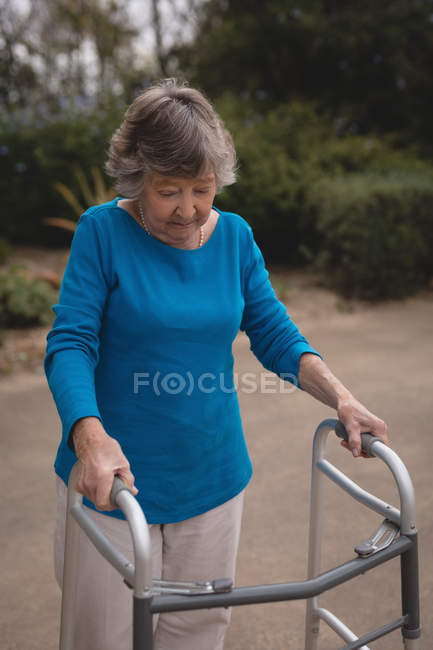 Senior woman walking with the help of walker — Stock Photo