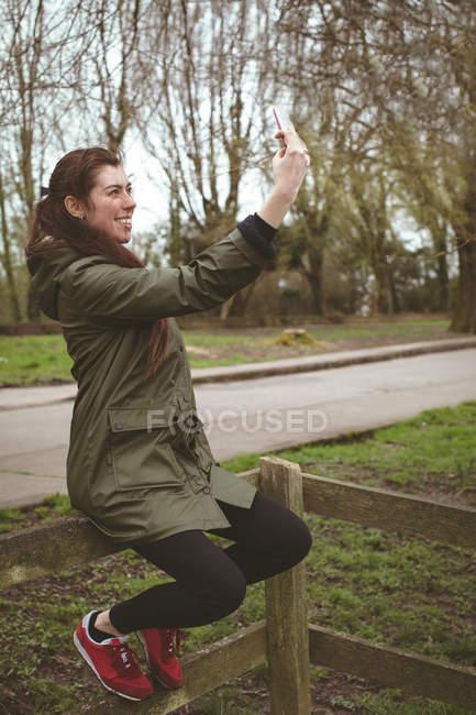 Красива жінка, беручи selfie з мобільного телефону в парку — стокове фото