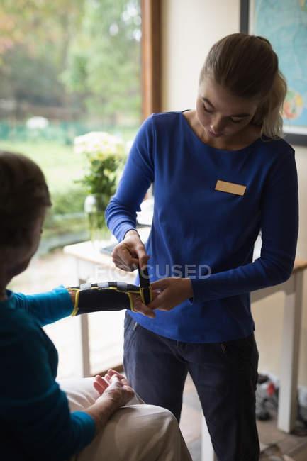 Physiotherapeuten setzen auf eine Handgelenkbandage Unterstützung auf ältere Frau zu Hause — Stockfoto