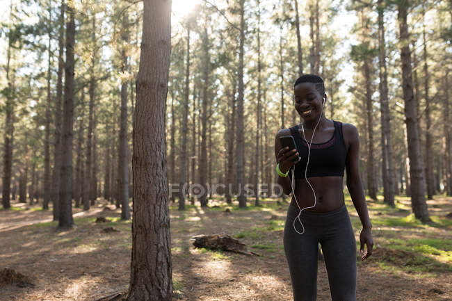 Smiling female athlete listening to music from smartphone mp3 player — Stock Photo