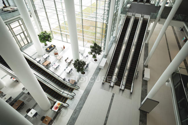 High angle view of escalators and pillars in the office — Stock Photo