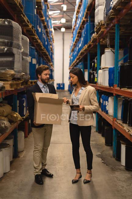 Сотрудники, обсуждая над запасы на складе — стоковое фото