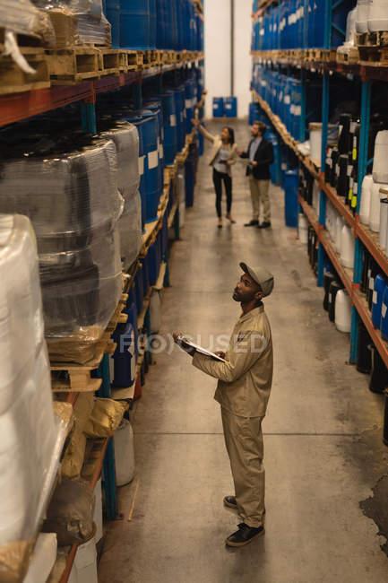 Работник мужского пола проверяет акции на складе — стоковое фото