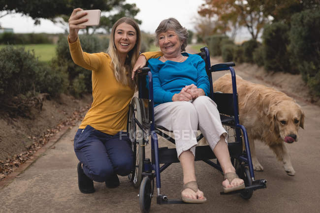 Beautiful granddaughter and grandmother taking a selfie on mobile phone — Stock Photo