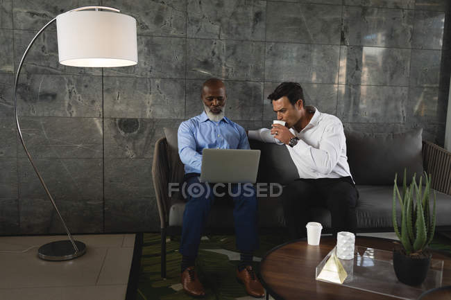Two businessmen having coffee and discussing over laptop — Stock Photo