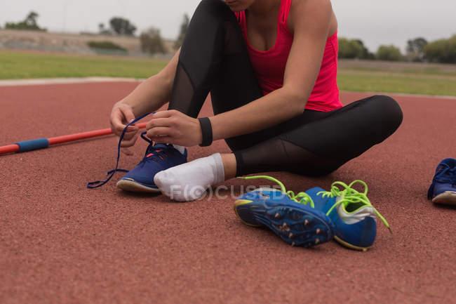 Спортсмен завязывает шнурки на спортивных площадках — стоковое фото