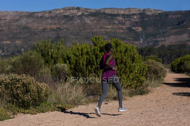 Atleta feminina determinada correndo na floresta — Fotografia de Stock