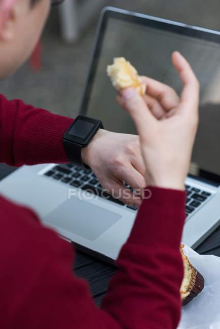 Sezione media dell'uomo che controlla il tempo sullo smartwatch al caffè all'aperto — Foto stock