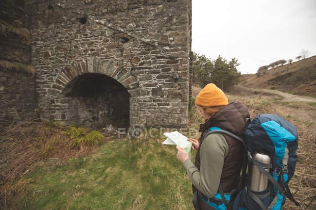 Joven excursionista leyendo un mapa - foto de stock