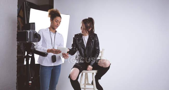 Fotografo femminile che discute su tablet digitale in studio fotografico — Foto stock