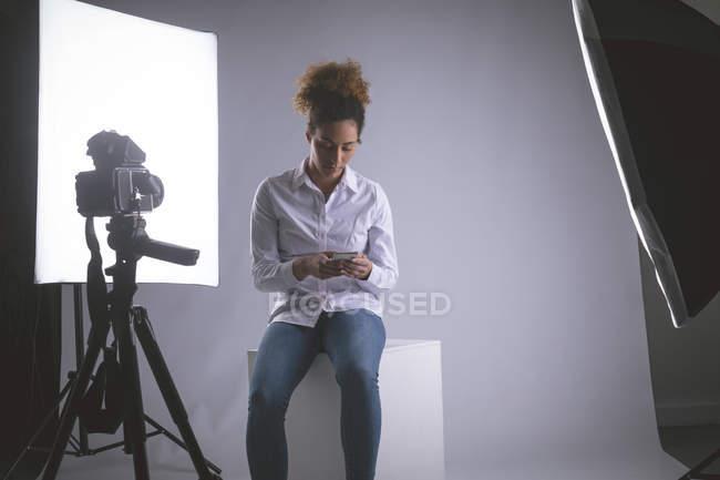 Fotógrafa feminina usando telefone celular no estúdio de fotografia — Fotografia de Stock