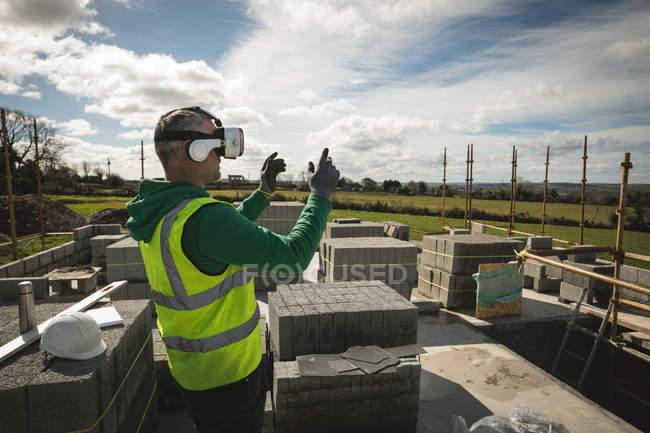 Ingénieur expérimentant casque VR sur le chantier de construction par une journée ensoleillée — Photo de stock