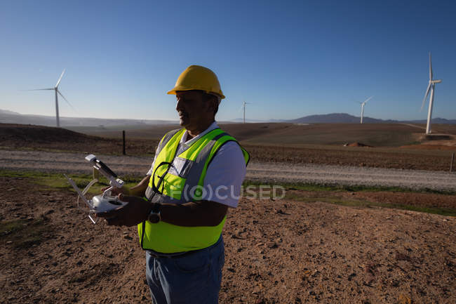 Ingénieur exploitant un contrôleur de drones dans un parc éolien — Photo de stock