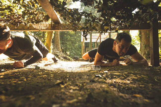 Fit men crawling under the net during obstacle course at boot camp — Stock Photo