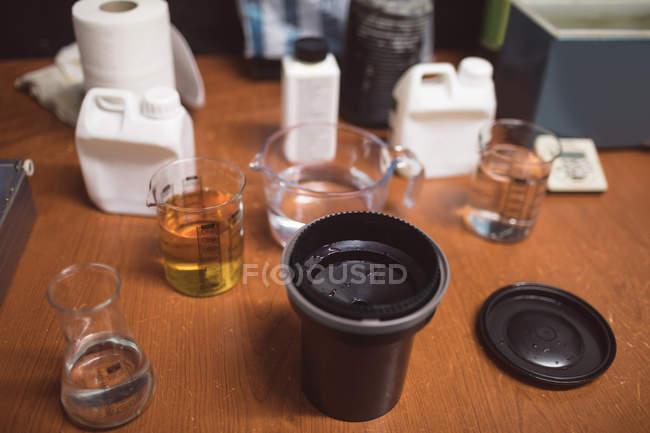 Крупным планом камеры крышка объектива с жидкостью на столе — стоковое фото