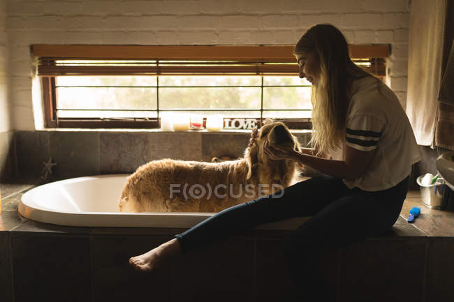Girl cleaning a dog in bathroom at home — Stock Photo