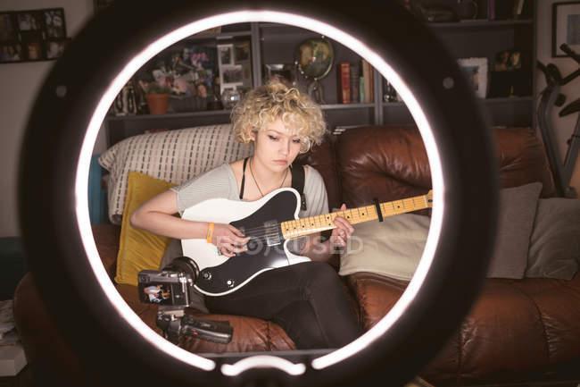 Blogueira feminina tocando guitarra na sala de estar em casa — Fotografia de Stock
