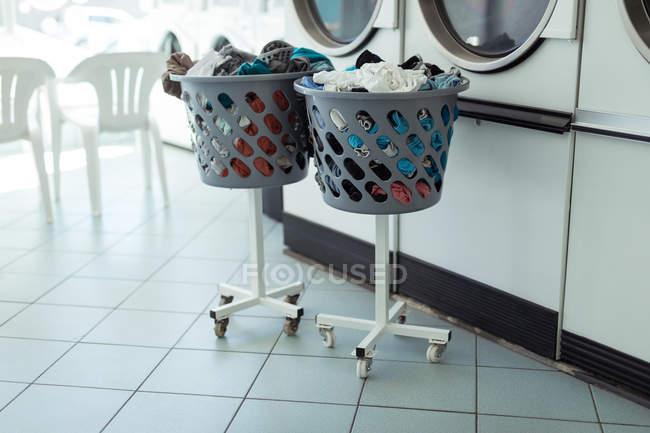 Two laundry baskets near the washing machine at laundromat — Stock Photo