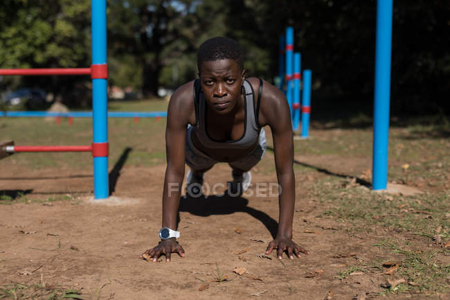 Determined female athlete doing push ups in the forest — Stock Photo