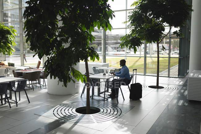 Uomo d'affari concentrato utilizzando il computer portatile in mensa ufficio — Foto stock
