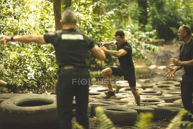 Homens aptos a treinar sobre pneus curso de obstáculo no acampamento de inicialização — Fotografia de Stock