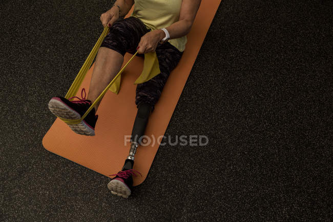 Disabled woman exercising with resistance band in the gym — Stock Photo
