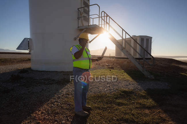 Engineer using a laptop at wind farm — Stock Photo