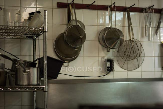 Stahlsieb hängt an Haken in Küche im Restaurant — Stockfoto