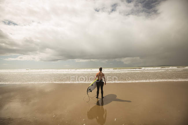 Rear view of surfer with surfboard looking at the sea from beach — Stock Photo