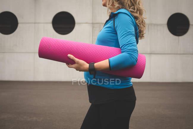 Mittleren Bereich schwangere Frau mit Gymnastikmatte — Stockfoto