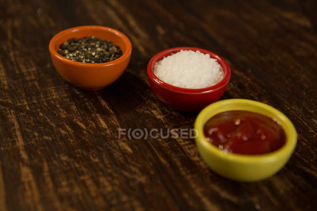 Sauce and salt in bowl on wooden table — Stock Photo