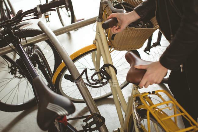 Donna che parcheggia la sua bicicletta al cavalletto — Foto stock