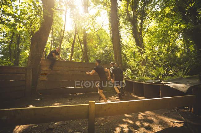 Entraînement des hommes sur le parcours d'obstacles au camp d'entraînement — Photo de stock
