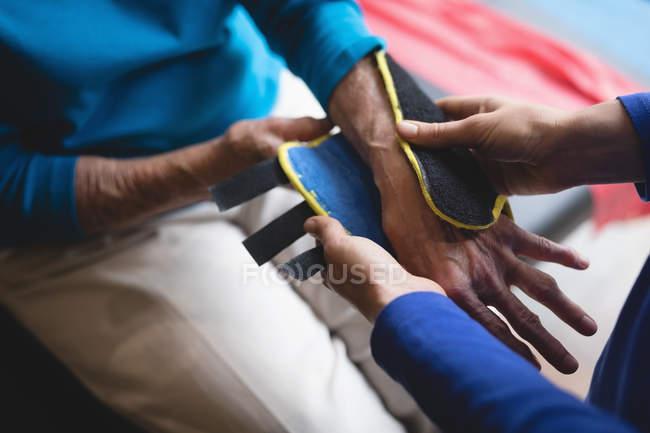 Nahaufnahme des Physiotherapeuten setzen auf eine Handgelenkbandage Unterstützung auf ältere Frau — Stockfoto