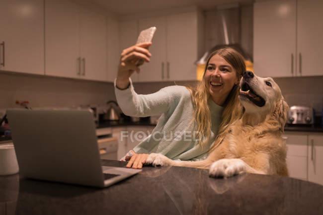 Девушка делает селфи со своей собакой на кухне дома — стоковое фото