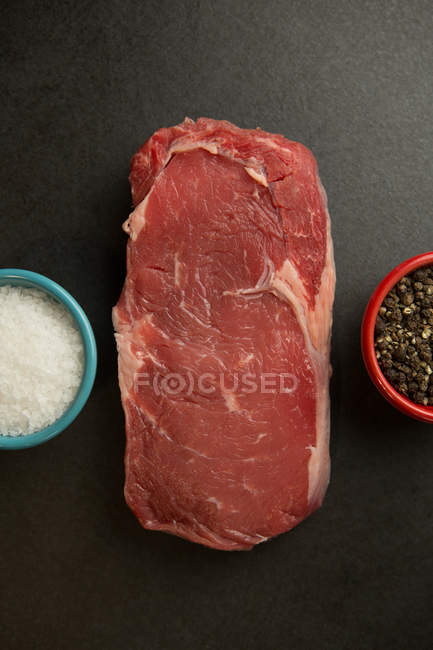 Close-up of meat with species on concrete background — Stock Photo