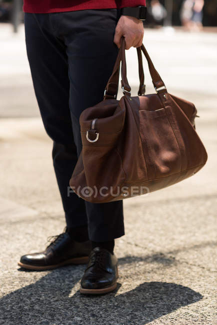 Low section of man standing with bag in the street — Stock Photo