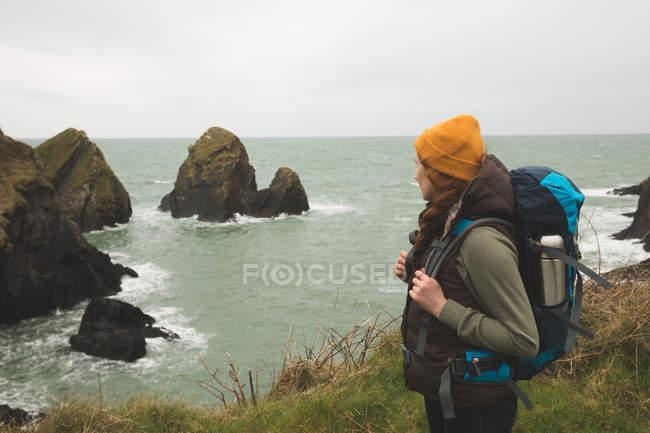 Vista laterale di escursionista femminile guardando il mare mentre in piedi sulla costa — Foto stock