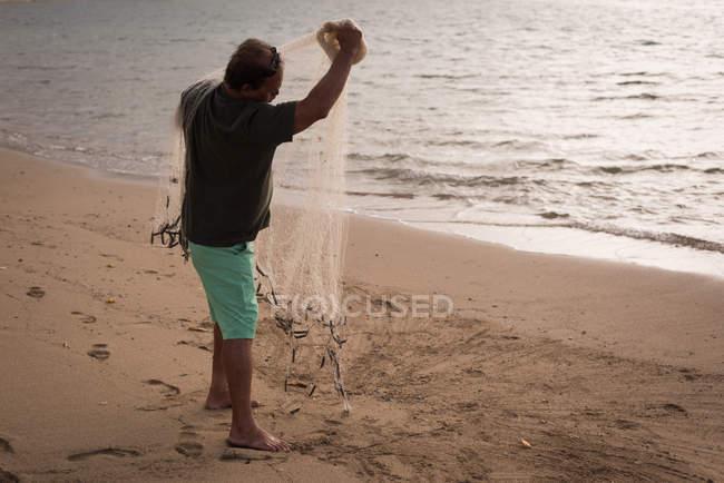 Pescador pesca em uma praia ao entardecer — Fotografia de Stock