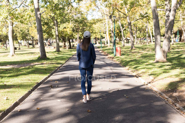 Rear view of woman standing on the road in the park — Stock Photo