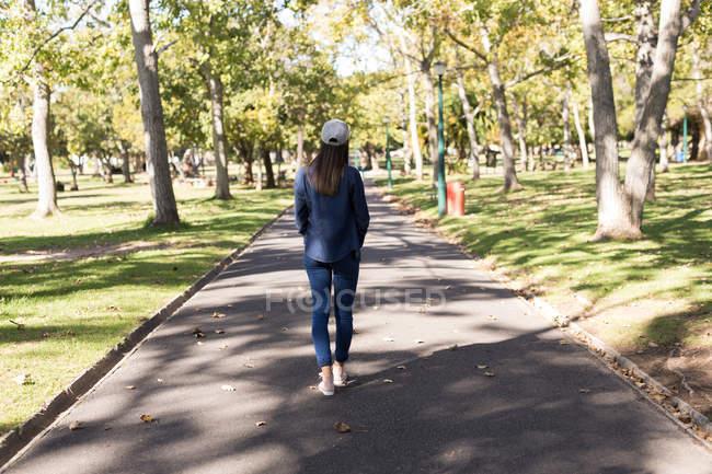 Vista traseira da mulher em pé na estrada no parque — Fotografia de Stock