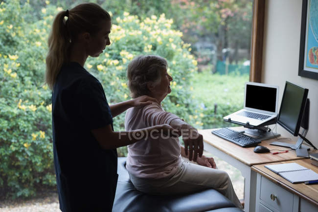 Physiotherapist giving a hand massage to senior woman — Stock Photo
